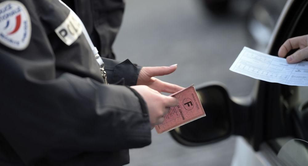 Un officier de patrouille de route vérifie des documents du conducteur (image d'illustration)