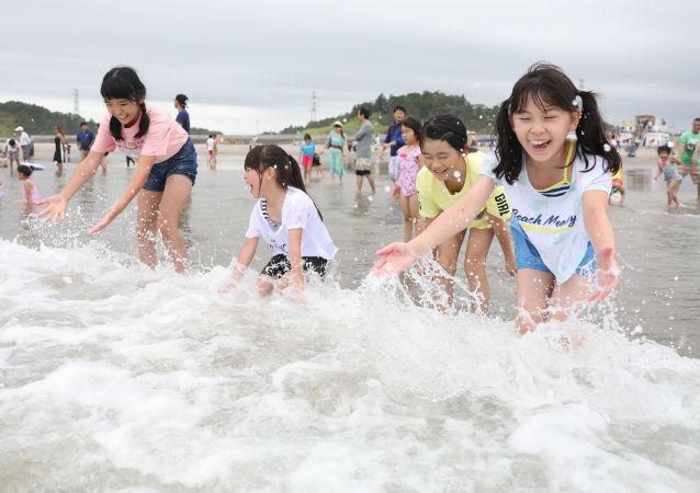 Des enfants jouent avec des vagues à la plage  de Kitaizumi,  dans la préfecture de Fukushima, le 20 juillet 2019.