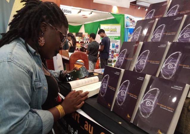 Une lectrice feuilletant le livre de Lamazone Wassawaney à l'édition 2019 du SILA à Abidjan