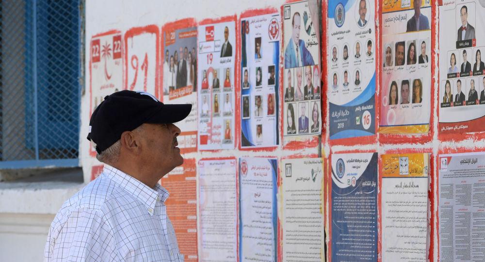 Un Tunisien devant les affiches des différents candidats aux législatives tunisiennes