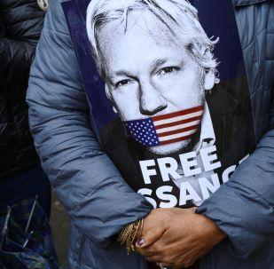 Une affiche dans les mains d'un participant au rassemblement en faveur de Julian Assange près du bâtiment du Tribunal de Westminster à Londres