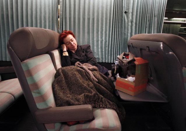 Une passagère couchée dans un train