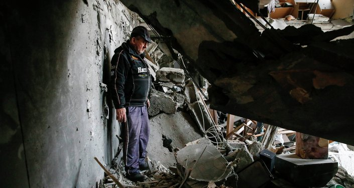 Un homme regarde les débris à l'intérieur d'un appartement à un bloc résidentiel endommagé par un pilonnage récent