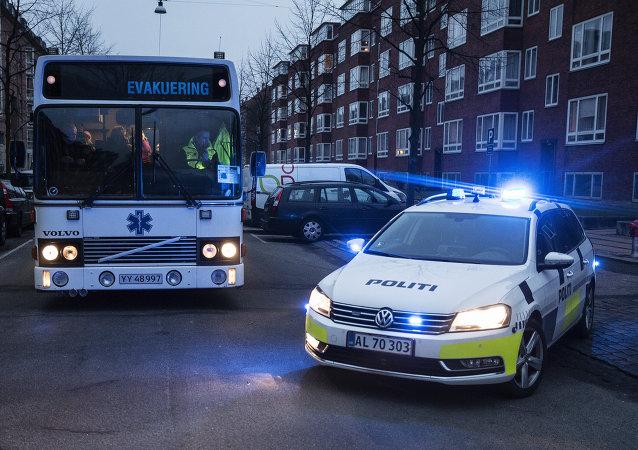 Les policiers utilisent un bus pour évacuer des témoins du site d'une fusillade à Copenhague samedi, le 14 février 2015