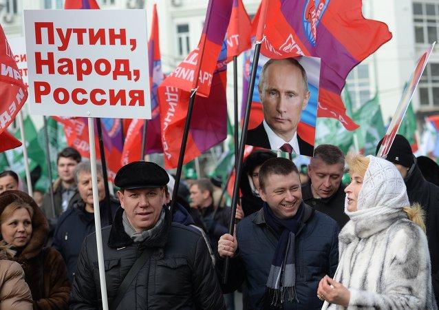 Des gens tiennent l'image du Président russe Vladimir Poutine lors de la marche Anti-Maidan