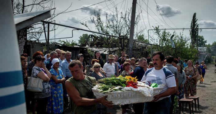 Les habitants du village de Louganskaïa (l'est de l'Ukraine) assistent à l'enterrement de leurs voisins tués dans un bombardement