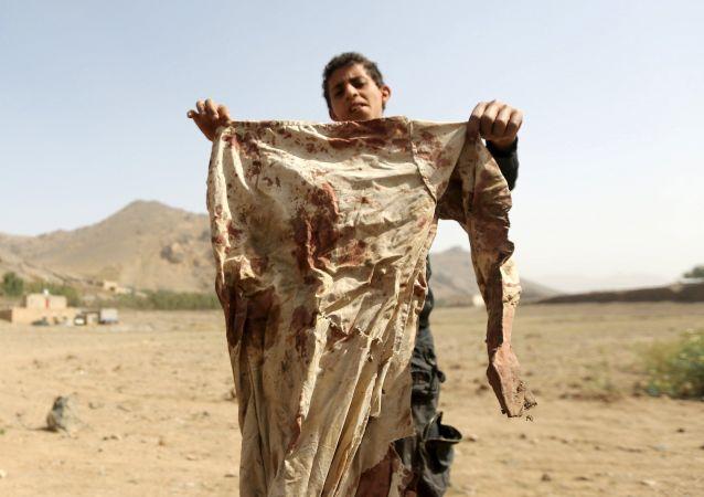 Le garçon tient les vêtements ensanglantés après l'attaque aérienne à Sana