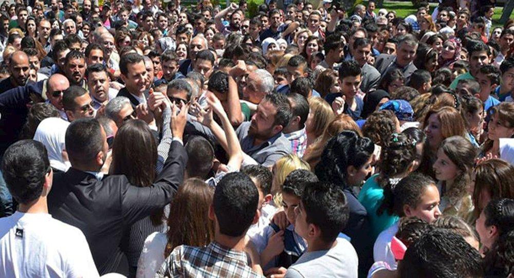 Le président Bachar al-Assad salue ses partisans lors d'un événement pour commémorer les martyrs dans une école le 6 mai 2015