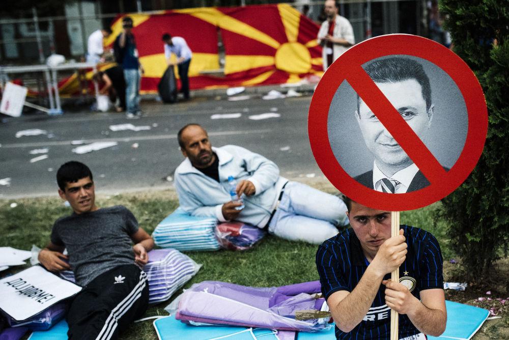 Les opposants, qui se sont installés devant le siège du gouvernement macédonien, tiennent des portraits barrés du premier ministre Nikola Gruevski