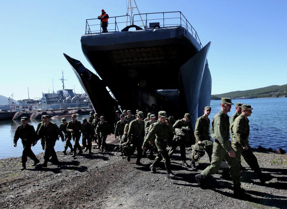 Un groupe de militaires réunis près du grand bâtiment de débarquement Oslabia