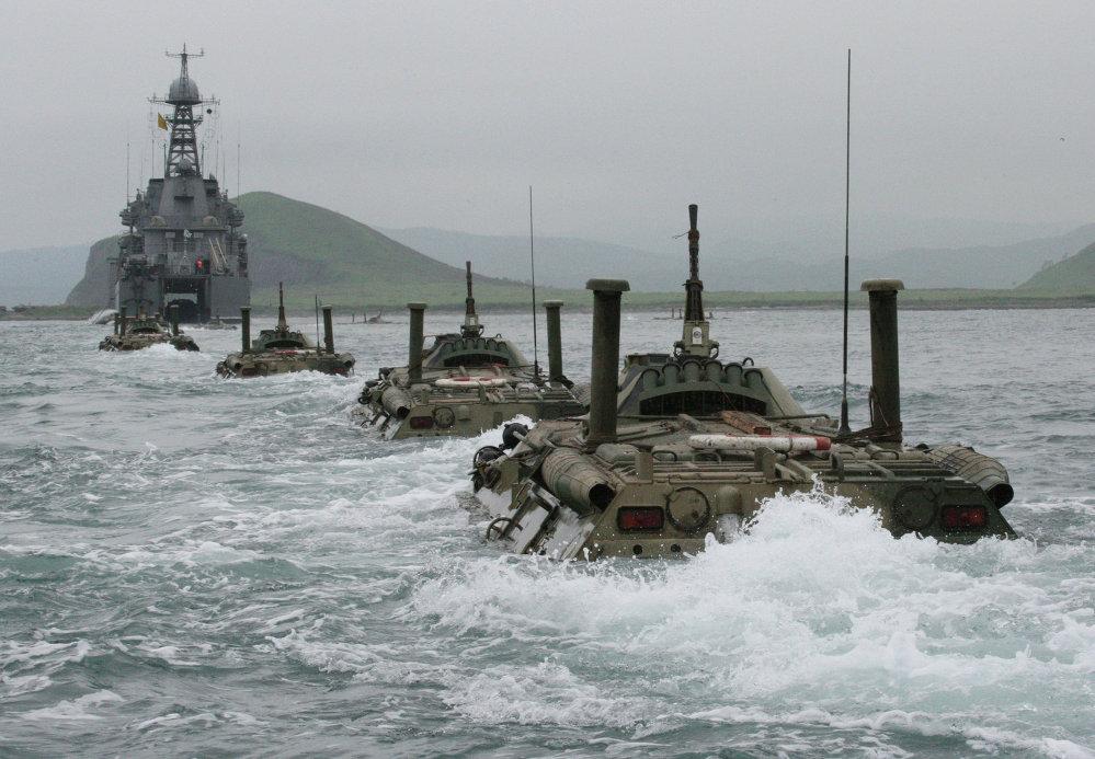 Des véhicules de transport de troupes se dirigeant vers un grand bâtiment de débarquement lors d'un exercice des marines de la Flotte russe du Pacifique