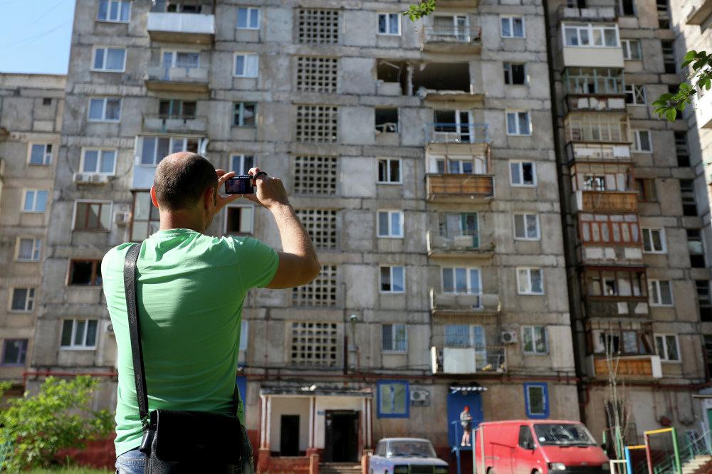 Un homme prend en photo un immeuble touché par les bombardements de Gorlovka, région de Donetsk