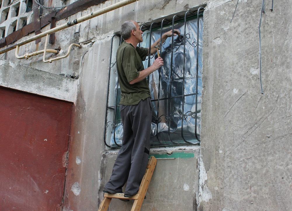 Un habitant de Gorlovka recouvre sa fenêtre brisée avec un film plastique, dans un immeuble touché par les bombardements de la ville
