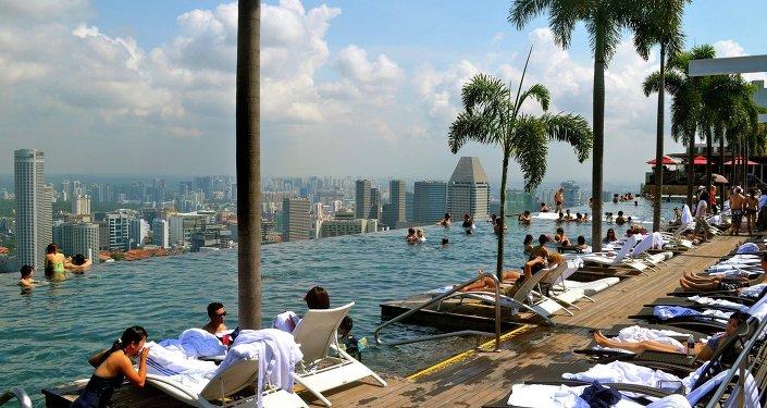 Des touristes près d'une piscine à Singapour.
