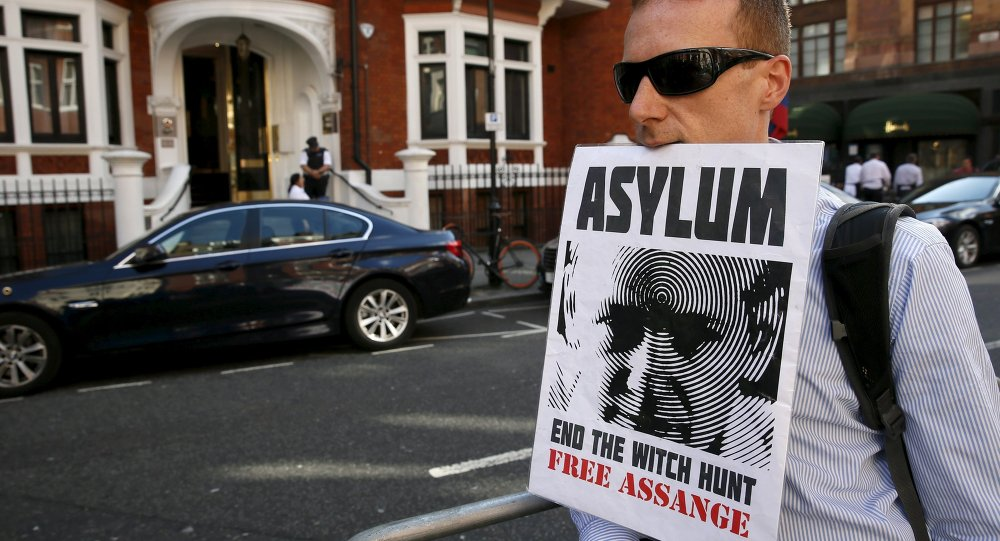 A supporter of Wikileaks founder Julian Assange holds a placard with his mouth during a gathering outside the Ecuador embassy in London, Britain June 19, 2015