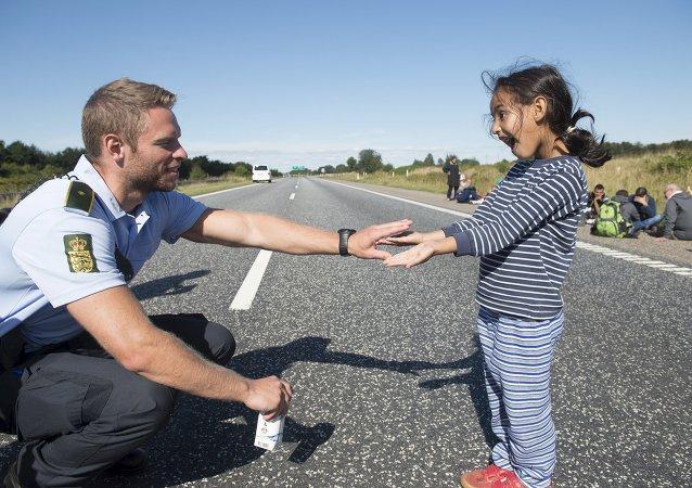 un policier danois avec une petite migrante