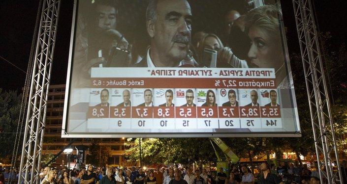 Un écran géant à Athènes montre les résultats des sondages sortie des urnes le 20 septembre