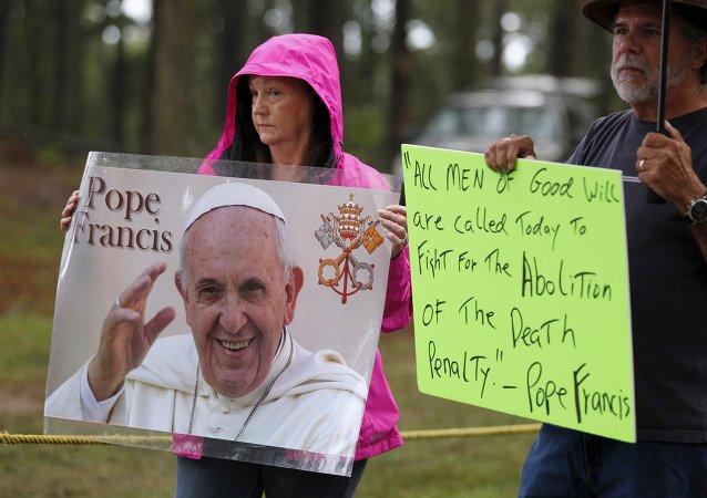 Supporteurs de Kelly Gissendaner tenant un portrait du pape François