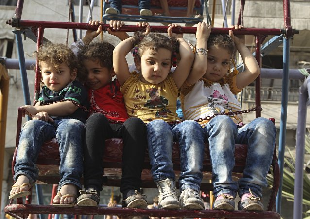 Children sit on a ferris wheel during Eid celebrations in Al-Fardous neighbourhood of Aleppo, Syria September 27, 2015.