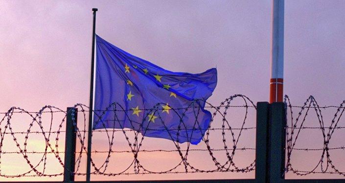 Le drapeau de l'UE derrière le fil de fer barbelé