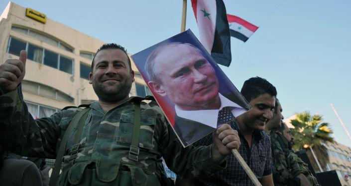 Un militaire syrien lors d'un rassemblement en faveur de l'opération russe en Syrie