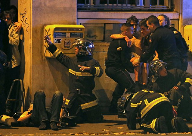 Des pompiers soignent un blessé devant la salle de concert du Bataclan
