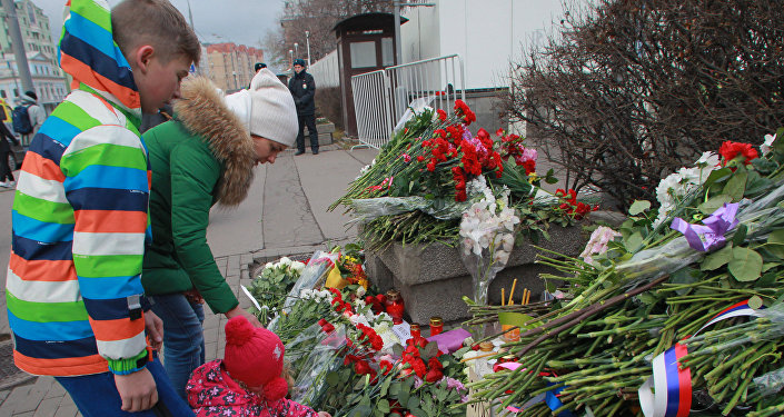 People lay flowers outside the French embassy in Moscow on November 14, 2015, to pay tribute to the victims of the deadly attacks in Paris
