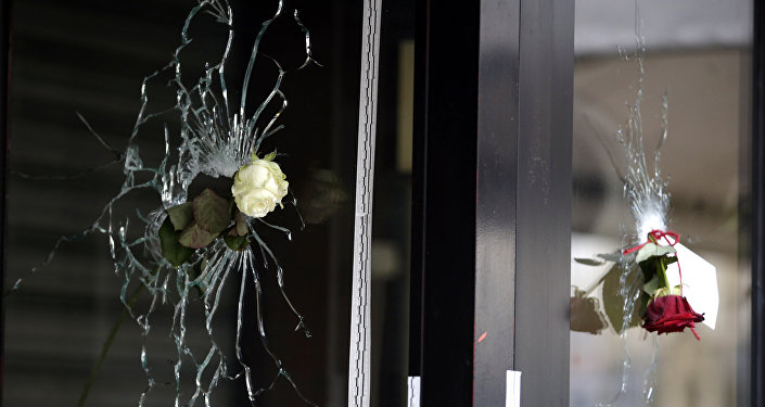 Roses are placed in bullet holes of the window of a Japanese restaurant along the Rue de Charonne in central east Paris, on November 15, 2015, two days after deadly attacks across the city
