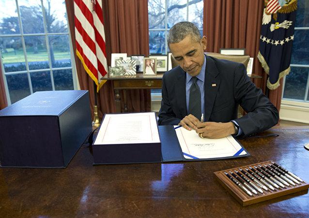 Le président Barack Obama signe le projet de loi budgétaire dans le Bureau ovale de la Maison Blanche