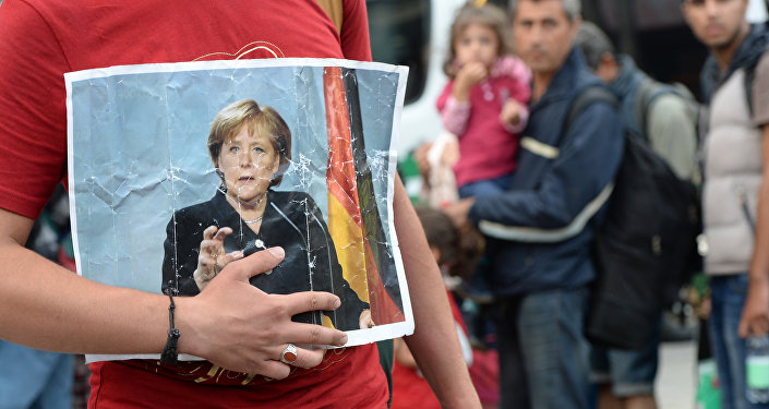 Un migrant tient le portrait d'Angela Merkel
