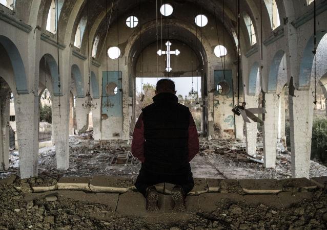 Un chrétien syrien prie dans l'église de Saint-Georges, détruite par Daech