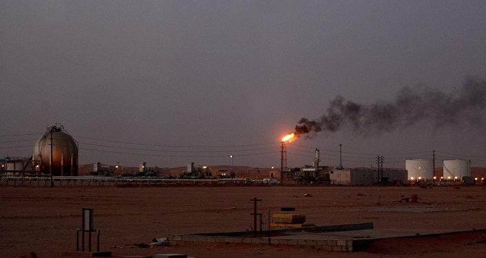 Une flamme d'une installation pétrolière de Saudi Aramco (la compagnie pétrolière nationale) appelée Pump 3 brûle brillamment au coucher du soleil dans le désert saoudien près de la zone riche en pétrole Al-Khurais, 160 km à l'est de la capitale Riyad