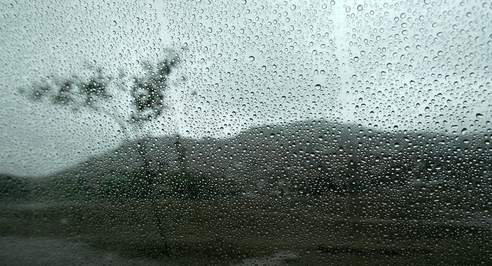 A landscape is seen through a wet window from inside a car in Lima