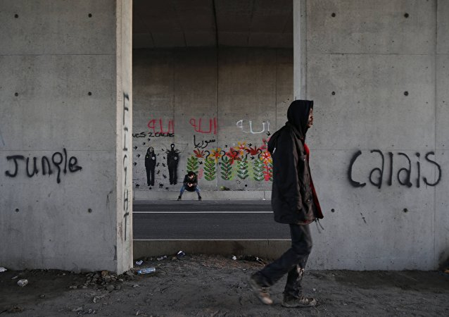Les immigrants font leur chemin le long d'une route près de graffiti avec les mots Jungle, Calais à Calais, France, le 20 Octobre 2015.