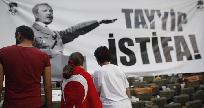 Un jeune manifestant portant un drapeau turc devant une bannière avec le Premier ministre turc Recep Tayyip Erdogan, présenté comme Adolf Hitler dans Gezi parc près de la place Taksim à Istanbul, le vendredi 7 Juin, 2013