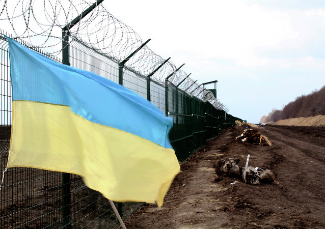 In this photo taken on Saturday, April 18, 2015, a Ukrainian national flag is attached to the fence on the Ukrainian-Russian border near Hoptivka, Kharkiv region, eastern Ukraine