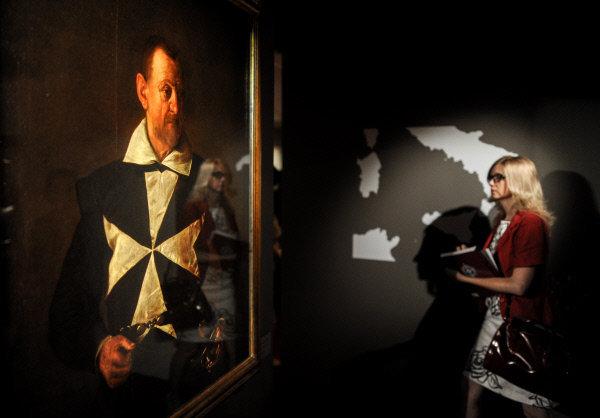 Sur la photo : un visiteur devant Le portrait du cavalier de l'ordre de Malte du Caravage à l'exposition « Le trésor de l'ordre souverain de Maltе. Neuf siècles au service de la foi et de la miséricorde » dans le palais du Patriarche.