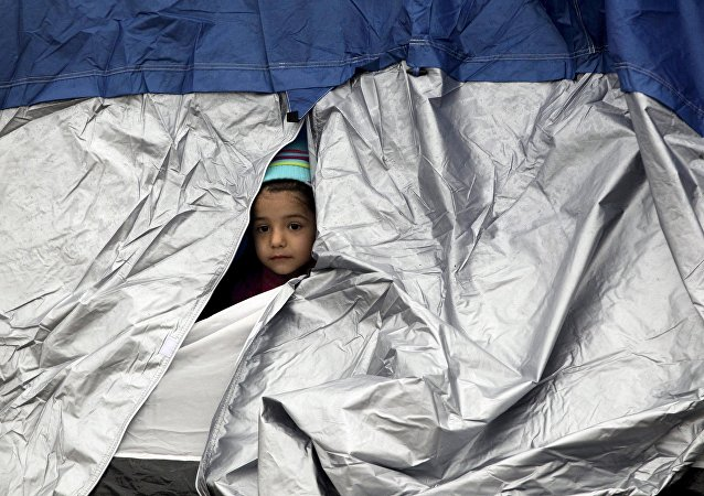 A child looks through a tent at a makeshift camp set up by stranded refugees and migrants