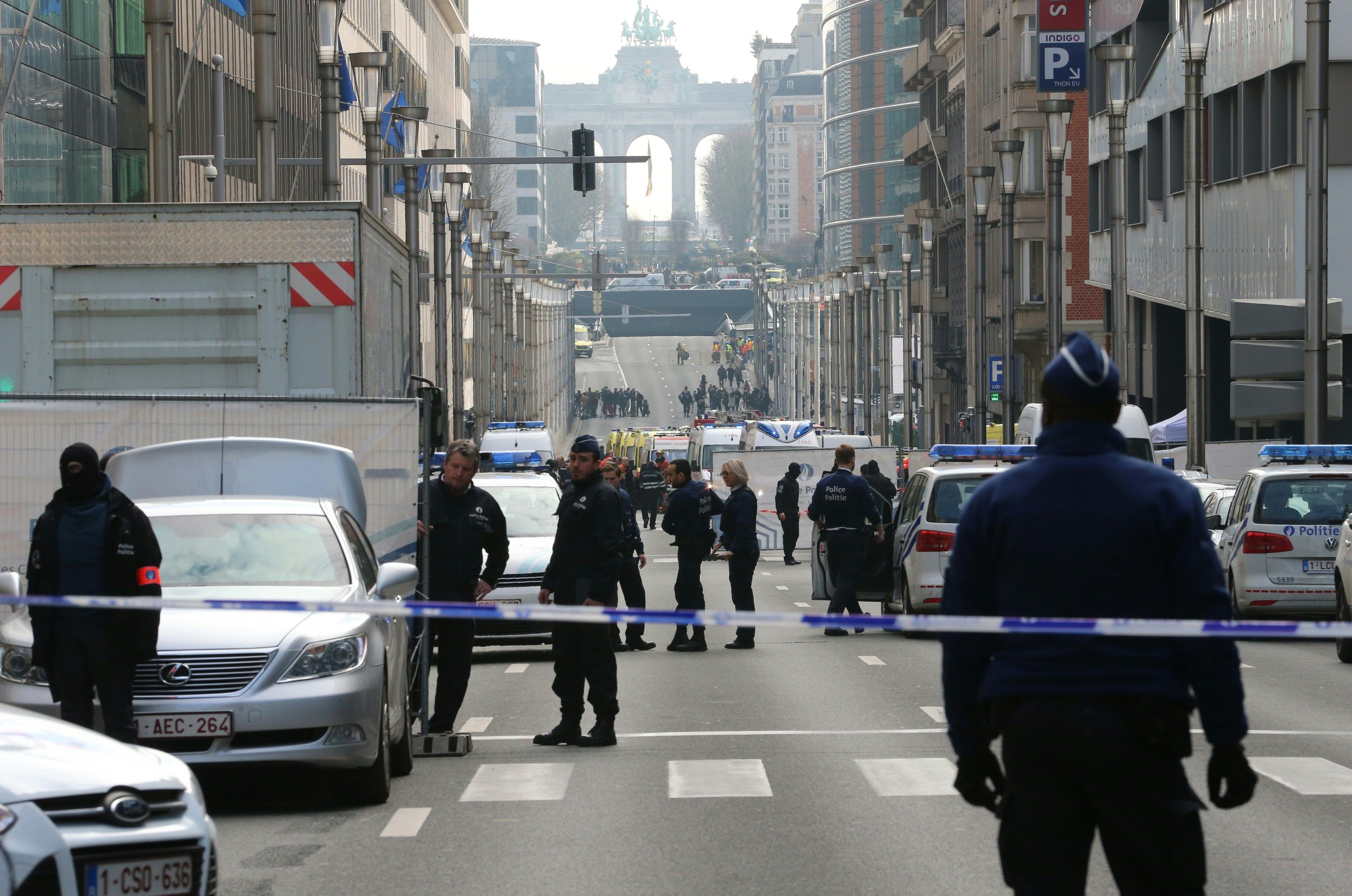 Policemen stand guard near a security perimeter set in the Rue de la Loi near the Maalbeek