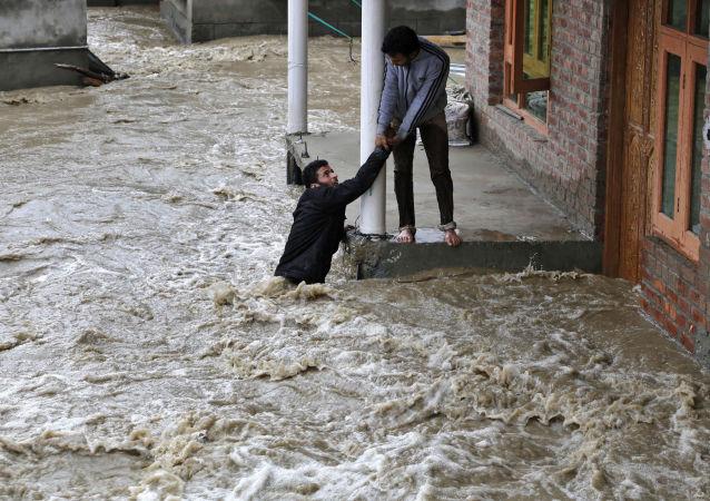 Un homme kashmirien tend la main pour aider une évacuer locale d'une zone touchée par les inondations à Srinagar, au Cachemire sous contrôle indien