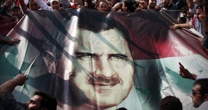 La foule tient un banderole à l'effigie du président Assad