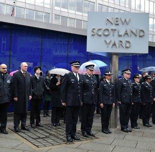 Des officiers de police britanniques observant une minute de silence en hommage à leurs collègues français tués lors des attentats de novembre 2015 à Paris