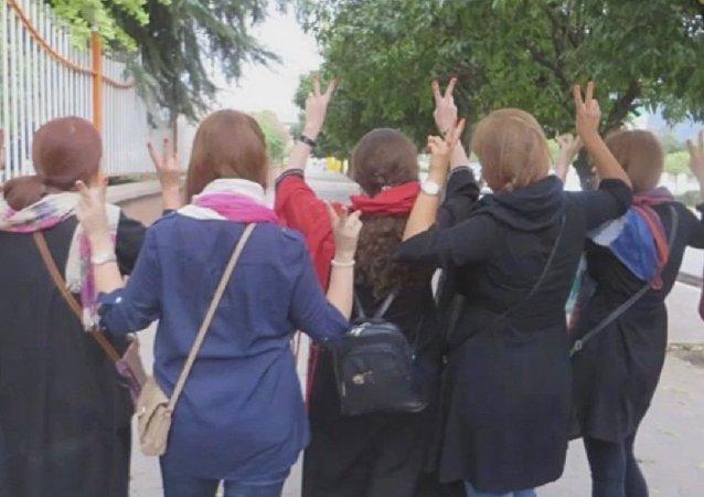 Jeunes Iraniennes protestant contre le port obligatoire du voile