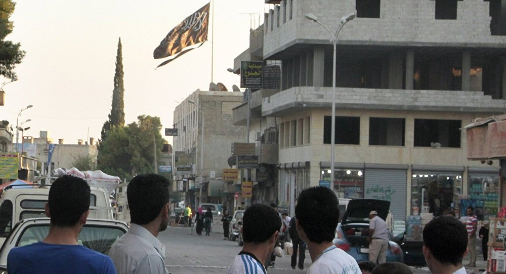 A group of men look at a large black Jihadist flag with Islamic writing on it proclaiming in Arabic that There is no God but God and Mohammed is the prophet of God, as they look over towards a building in the northern rebel-held Syrian city of Raqqa on September 28, 2013.
