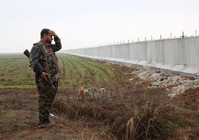Le soldat kurde près d'un mur mis en place par les autorités turques, à la frontière entre la Syrie et la Turquie en Syrie occidentale, le 2 Février, 2016