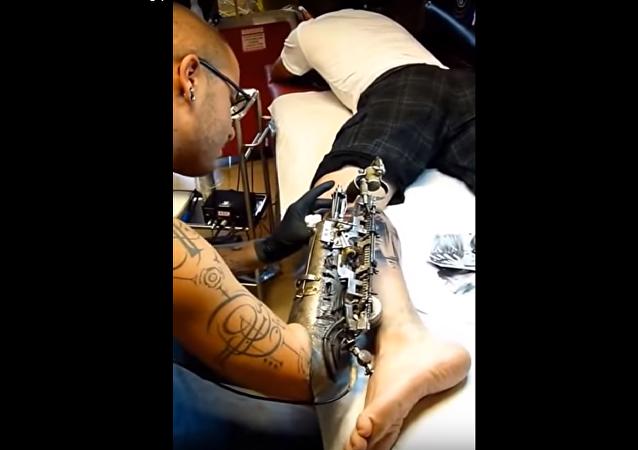 un tatoueur qui réalise son métier avec un bras biomécanique