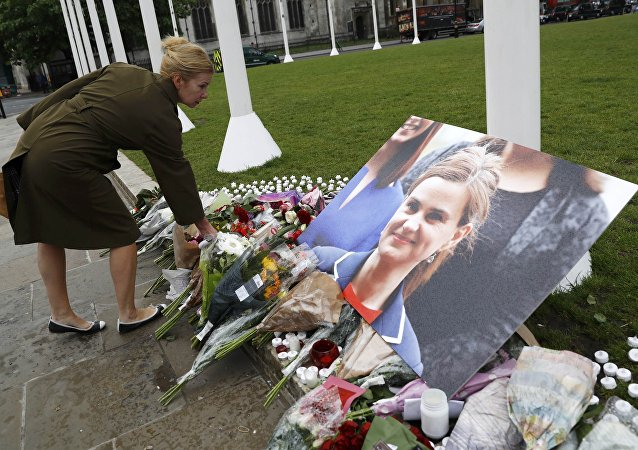 A woman leaves a floral tribute next to a photograph of murdered Labour Member of Parliament Jo Cox in Parliament Square, London, Britain June 17, 2016
