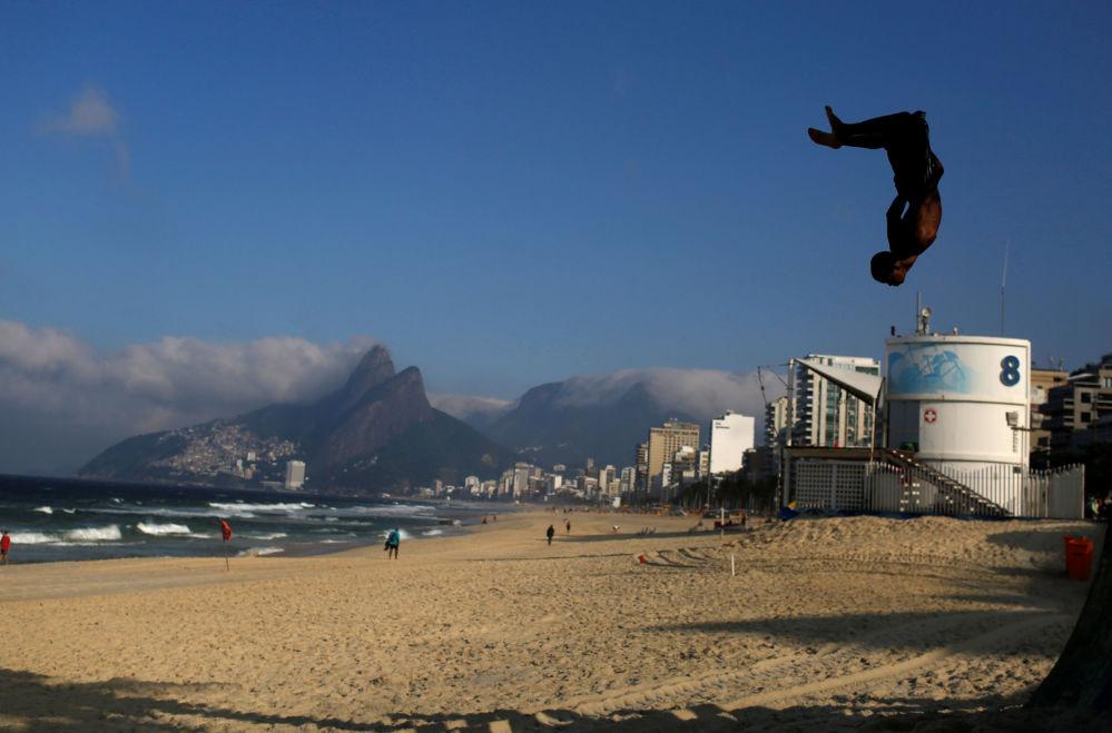 Un jeune homme fait du parcours sur la plage d'Ipanema à Rio de Janeiro