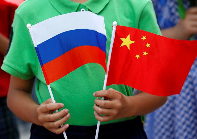 Un enfant tient des drapeaux russe et chinois lors de la cérémonie d'accueil du président russe Vladimir Poutine à Pékin