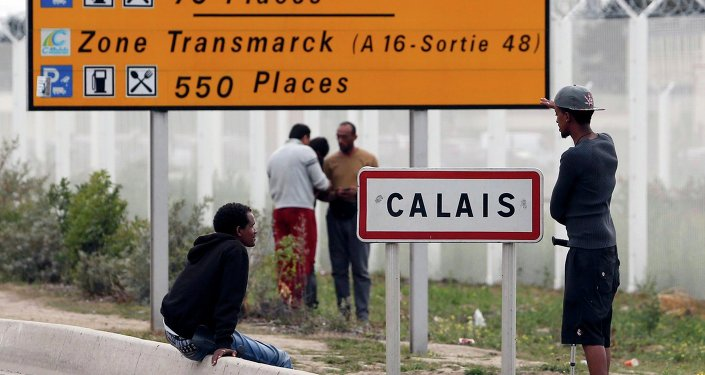 Migrants stand near a city sign along a road near the makeshift camp called The New Jungle in Calais, France, August 19, 2015